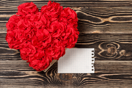 title emotions: Handmade flowers in box with valentine card on brown wooden background Stock Photo