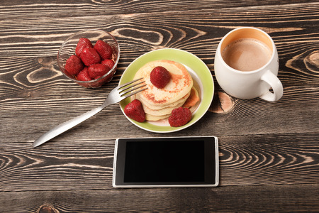 smartphone, cup of coffee, Pancakes, strawberries on brow wooden table