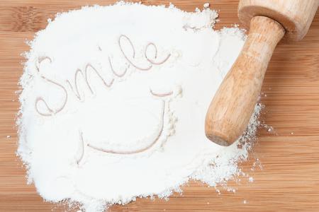 white flour: smile word on white flour. wooden table. Flat lay.