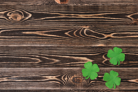 clovers: Four leaf clovers on brown wooden background