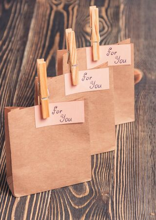 folded paper: Blank folded paper bag against brown wooden background Stock Photo