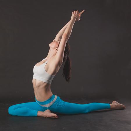 yogi: Beautiful sporty yogi girl practices yoga asana over black background Stock Photo