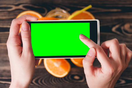 green screen: Hands Taking Photo of Juice and Oranges on Wooden Background. Green Screen. Technology Concept