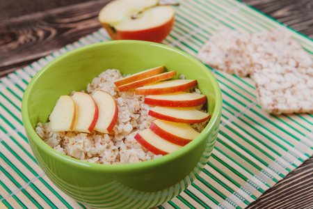 childrens food: Oatmeal Porridge with Apple Slices in Green Bowl. Healthy Food Concept