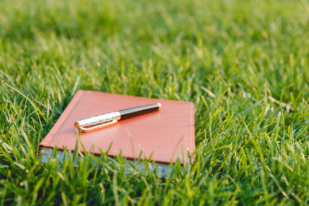 note booklet: Pen and Notebook on Fresh Green Grass. Education Concept