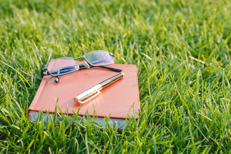 note booklet: Pen, Glasses and Notebook on Fresh Green Grass. Education Concept