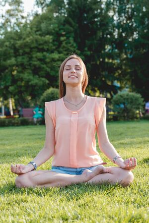 Young Woman Sitting in Lotus Position on Nature. Healthcare Concept Stock Photo
