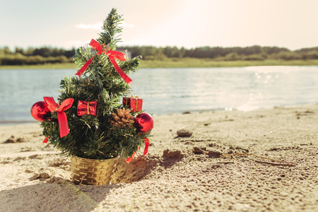 artificial lights: Christmas tree on the sandy beach. Christmas vacation concept. Stock Photo
