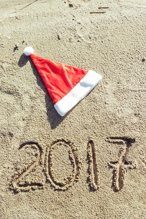 santa clause hat: 2017 inscription written on sandy beach and santa clause hat. new year concept