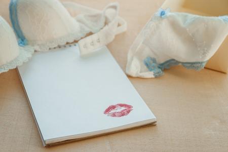 Leerer Notizblock mit womans Unterwäsche auf Holztisch Standard-Bild - 74065520