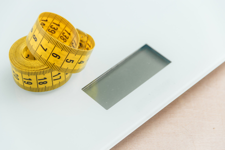 weigher: Curved measuring tape. Closeup view of yellow measuring tape on weigher