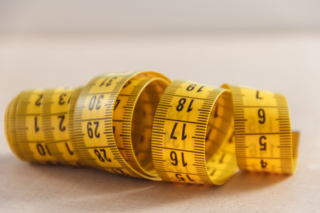 turn table: Curved measuring tape. Closeup view of yellow measuring tape. Stock Photo