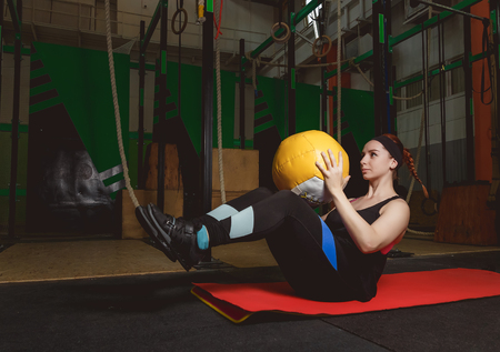 physique: Work out fitness woman doing sit ups exercises with medecine ball. Stock Photo
