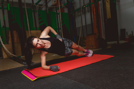 Attractive young woman is doing plank exercise while working out in gym.