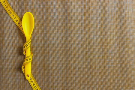 Spoon tied with tape measure. diet concept
