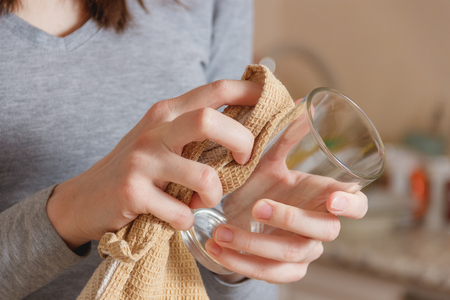 Female Hand Wipes Clean Glass by Tap in Kitchen. Housework, Spring Cleaning Concept.
