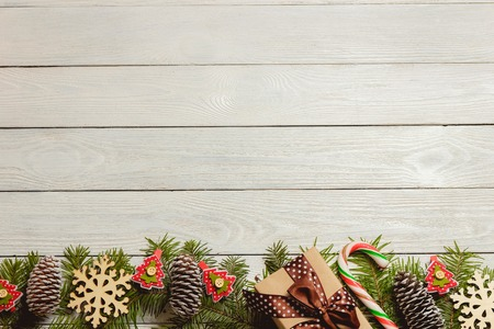 White wooden christmas background with fir branches, cones, decor, top view, copyspace.