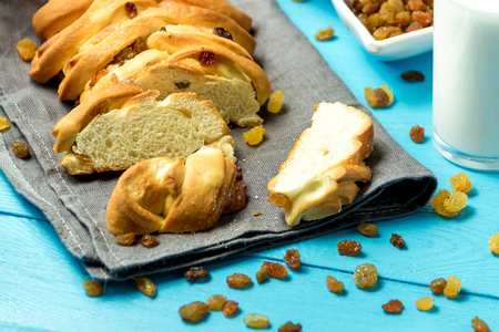 Piece of Sweet Braided Bread with raisins on kitchen towel on blue wooden background. Stockfoto