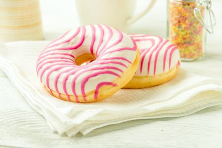 Donut on a kitchen towel and on a wooden table. Photo of sweets. Stock Photo