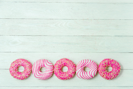 Row of donut on white wooden table. Photo of sweets with copyspace. Top view.
