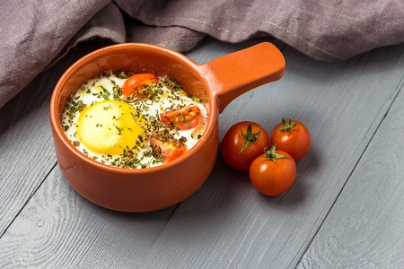 Portioned baked eggs in ceramic cocotte on gray wooden table, breakfast. Stok Fotoğraf