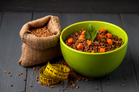 Green bowl of tasty buckwheat porridge on gray wooden table. The concept of a healthy diet. Stock Photo