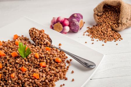 White plate of tasty buckwheat porridge on white wooden table.