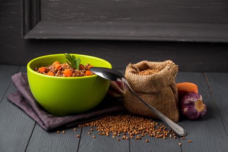 Green bowl of tasty buckwheat porridge on gray wooden table.