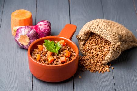 Brown bowl of tasty buckwheat porridge on gray wooden table.