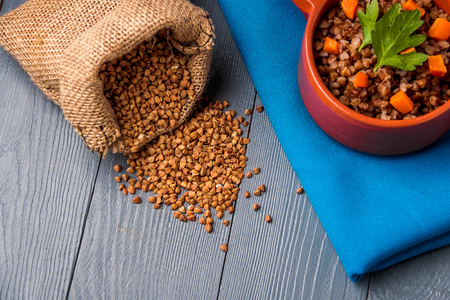 Brown bowl of tasty buckwheat porridge on gray wooden table. Top view.