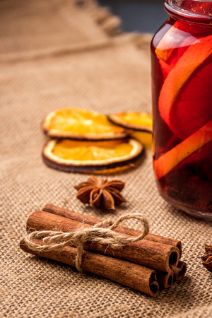 Mulled wine and spices on gray wooden background. Selective focus.