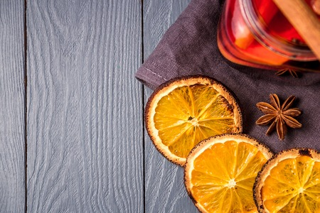 Mulled wine and spices on gray wooden background. Selective focus. Top view with copyspace.