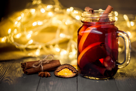 Mulled wine and spices on white wooden background. Selective focus.