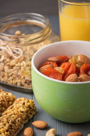 Granola cereal flakes with dried fruit, nuts in green bowl on gray wooden table. Imagens