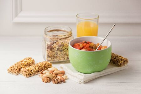Granola cereal flakes with dried fruit, nuts in green bowl on white wooden table. Imagens