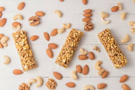 Granola bars cereal flakes with nuts on white wooden table. Top view. Imagens