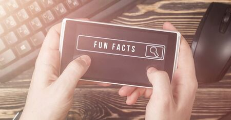 Interesting fact searching concept. Text FUN FACTS on smartphone screen. Banner. Stock Photo
