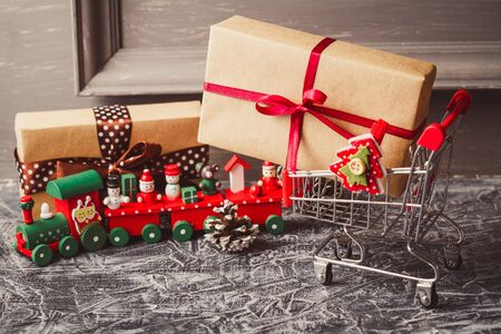 Shopping cart with gift or present on concrete table. Christmas and New year sale concept. Stock Photo