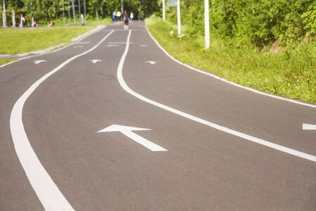 White forward arrow to finish on running track. Asphalt walk way in park. Stock photography.