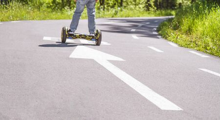 Boys legs on hoverboard. White forward arrow on running track. Asphalt walk way in park. Stock photography. Stock Photo