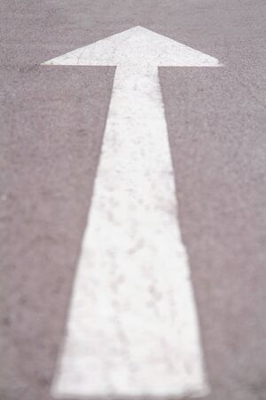 Close up white forward arrow on running track. Asphalt walk way in park. Stock photography.