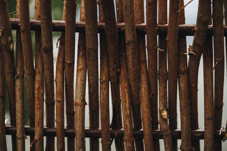 close-up of wooden gray with rods of an old wicker fence. Texture fo banner, poster with space for text. Stock Photo
