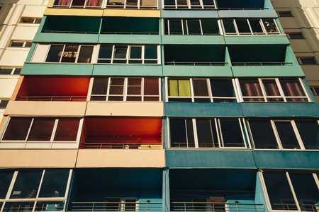 Residential Building Background. Colorful Facade of a modern housing construction with balconies.
