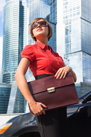 beautiful businesswoman holding a briefcase near the car on a background of skyscrapers