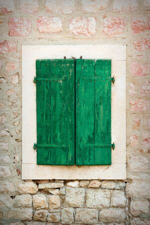 Closed wooden window on aged brick wall background
