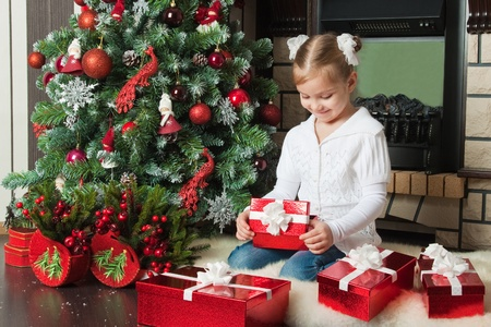 Funny girl with gifts near christmas tree and fireplace