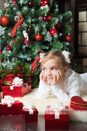 Little girl with gift lying and dreaming near christmas tree photo
