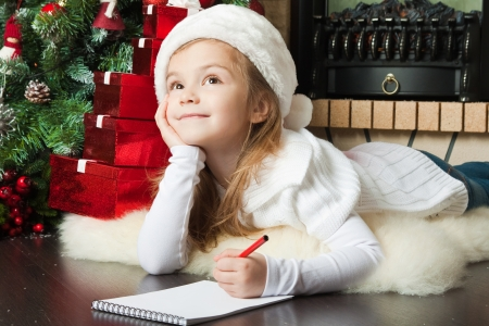 Funny girl in Santa hat writes letter to Santa near christmas tree photo