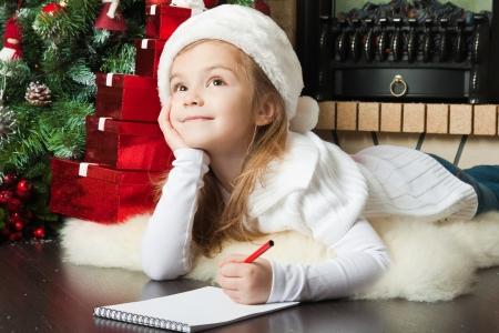letter box: Funny girl in Santa hat writes letter to Santa near christmas tree