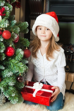Little girl in Santa hat holding a gift box near christmas tree